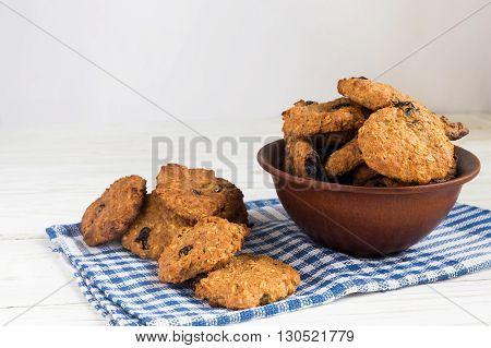 Freshly baked oatmeal raisin cookies in clay bowl on rustic wood background
