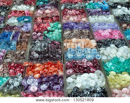 Various colorful buttons in plastic box for sell focus on the center of image.