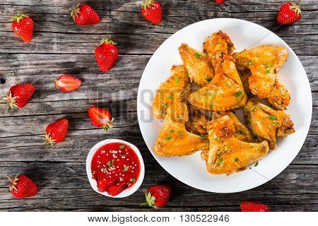 delicious fried chicken wings on a white dish with strawberry sauce on a gravy boat and strawberries on a wooden table studio lights top view