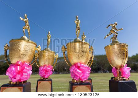 Track and Field trophies outdoor on a bright sunny day with selective focus on the nearest trophy blurred blue sky background