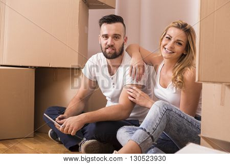 Young couple in love moving in a new apartment sitting on the floor planning to redecorate their new home