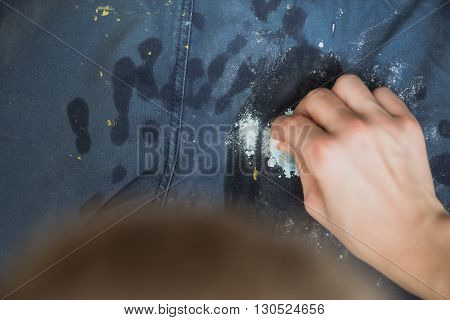 boy wipes the paint on his pants. Blue Jeans and sneakers stained with yellow paint. Top view