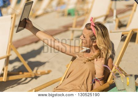 Beautiful blond lying on a sunbed on the beach taking a selfie with a tablet computer