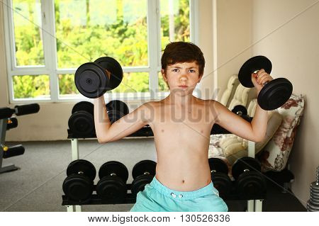 preteen boy training with dumbbells in gym