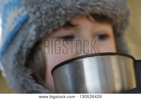 The boy the child in the forest. Fun in the fresh air. Drinking hot tea from a thermos