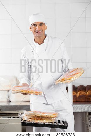 Baker Stacking Packed Pizza Breads In Bakery