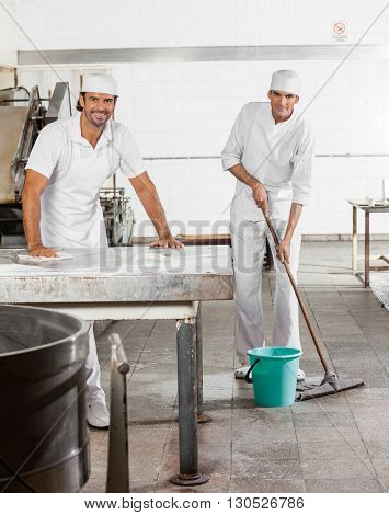 Confident Male Baker's In Uniform Cleaning Bakery