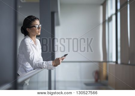 Strong confident business woman standing in an office building holding tablet computer