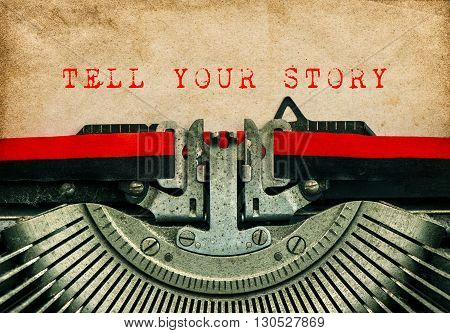 Old typewriter with sample text TELL YOUR STORY. Grungy paper background