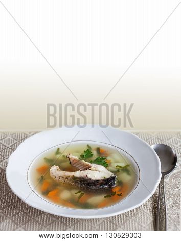 Mediterranean fish food concept. Vintage plate with carp fish soup and vegetables. sliced carp, potatoes, carrot, herbs
