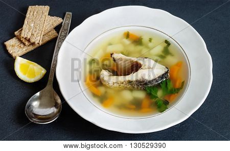 Mediterranean fish food concept. Vintage plate with carp fish soup and vegetables. sliced carp, potatoes, carrot, herbs. copy space