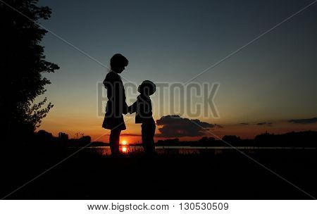 a silhouette of happy children on sunset