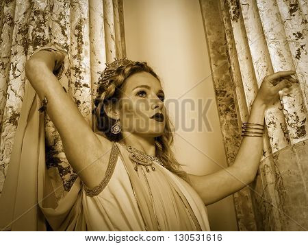 woman in traditional roman clothing posing in temple, sepia tone