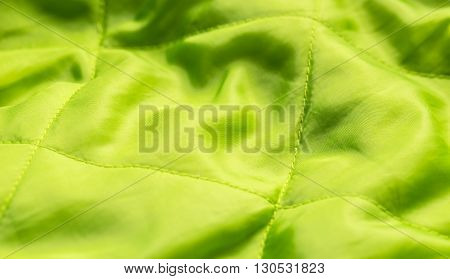 Green coat inside textile with seam, close up