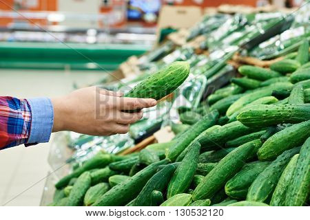 Buyer Selects Cucumber In Store