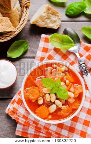 Thick soup with beans and vegetables on a wooden background. Selective focus.
