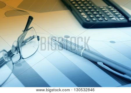 Business still life with pen glasses and calculator