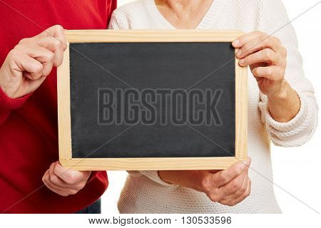 Old couple holding empty blackboard in their hands