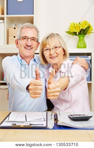 Happy senior couple holding thumbs up together for congratulation