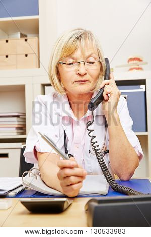 Old female doctor on call sitting in her office at the telephone