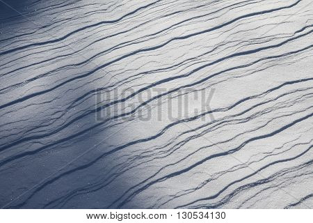 Layered snow dunes with blue shadows background texture