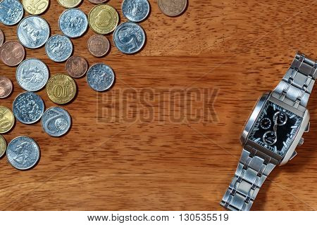 Men's wrist watch and metal coins as in time is money concept