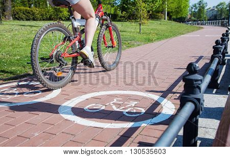 young girl bicyclist riding on the bike path outside on spring day