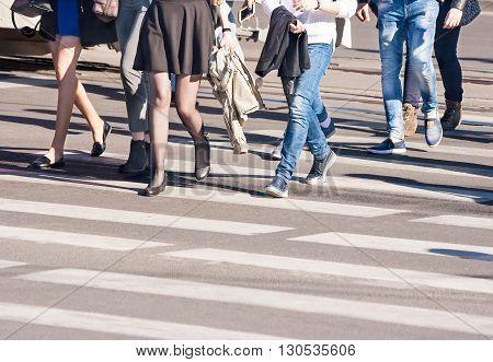 pedestrians walking on a crosswalk outside on sunny spring day