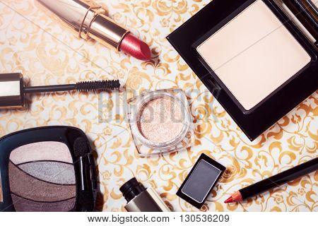 Makeup set of powder, smokey eyes and golden eyeshadows, mascara, red shiny lipstick and lip pencil
