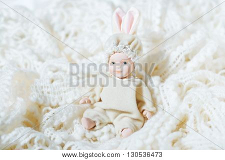 Ceramic doll newborn baby on a bright background