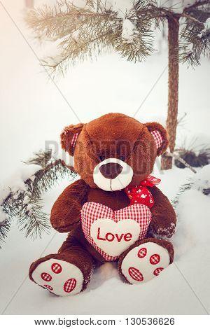 Fluffy cute soft toy teddy bear with heart love in snow closeup