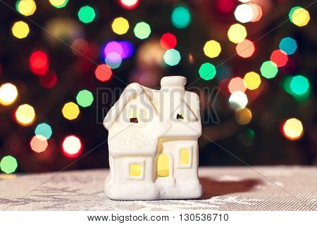 Glowing Christmas Toy house on a background of a New Year's garland. Blurred background, bokeh.
