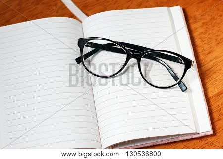 Open blank notebook and black folded  glasses