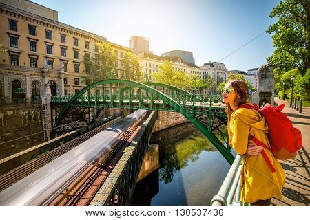 Woman enjoying view on the water channel with subway in Vienna