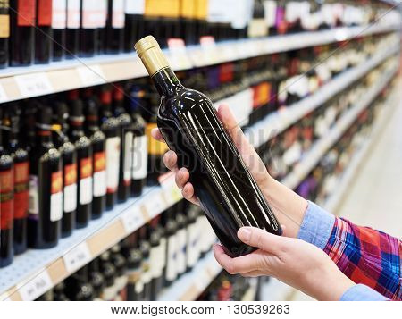 Woman With Bottle Of Red Wine In Store