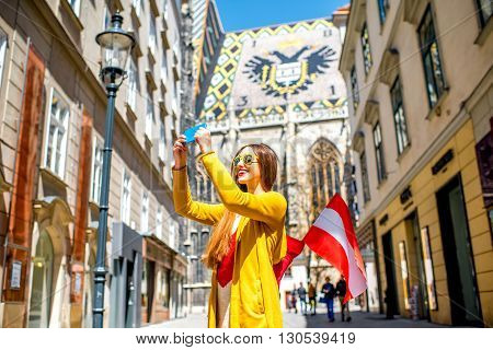 Young female tourist with austrian flag making selfie photo with Saint Stephen's cathedral in the center of Vienna