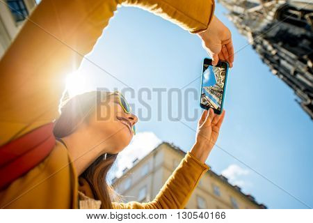 Young smiling woman photographing with phone St. Stephen's Cathedral tower in Vienna