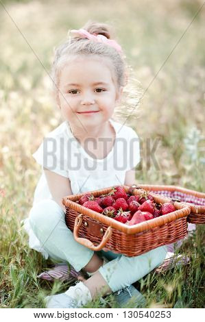 Cute baby girl 3-4 year old having picnic outdoors. Eating fresh strawberry. Looking at camera.