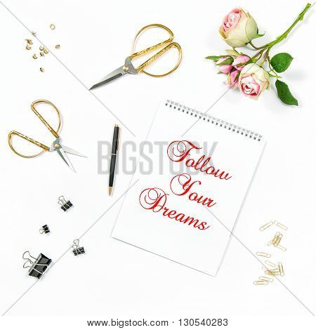 Flat lay with sketchbook rose flowers golden accessories on white background. Motivation quote Follow Your Dreams