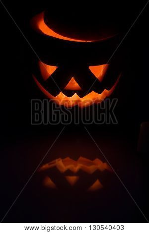 Scary Halloween pumpkin lantern ( jack-o'-lantern) with burning candle inside