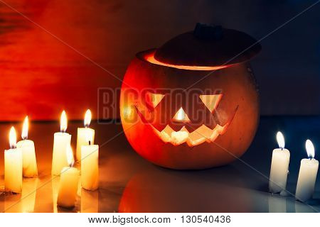Scary Halloween pumpkin lantern ( jack-o'-lantern) with burning candles on a dark wooden background