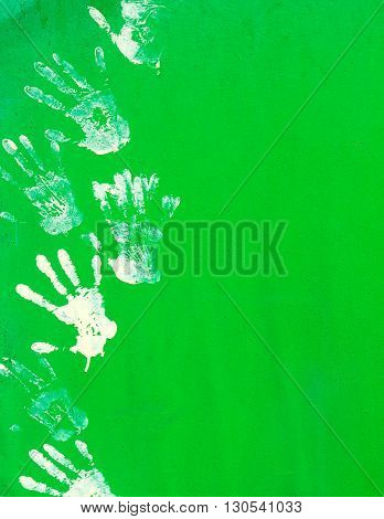 White paint hand print on green metal wall texture.