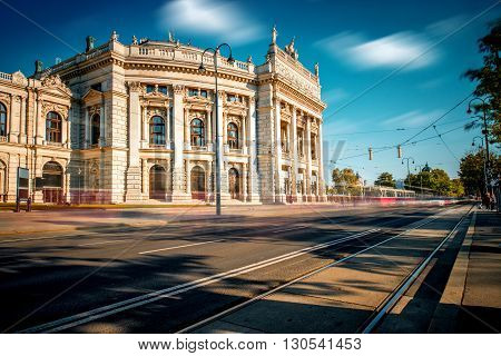 Burgtheater building with red tram in Vienna. Long exposure image technic with blurred cars and clouds