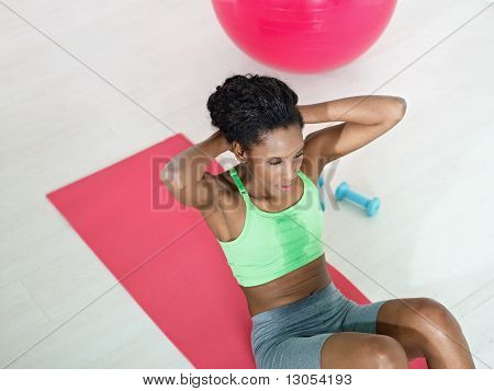 African Woman Doing Series Of Crunch In Gym