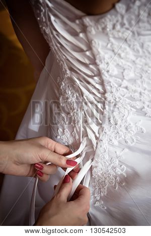 Bridesmaid tie the laces on the back of a wedding dress closeup