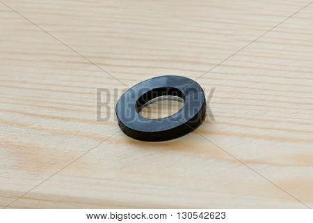 A single rubber spacer on a simple wooden background