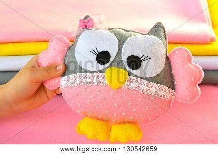 Children hand holds a felt toy owl
