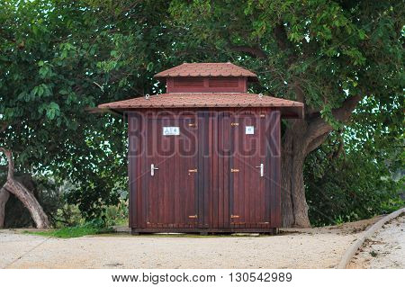Wooden public toilet among trees in park