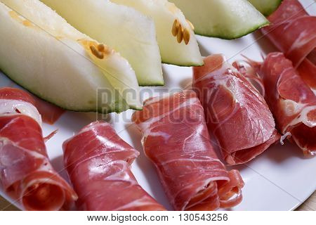 Closeup of slices of rolled cured pork ham jamon with melon