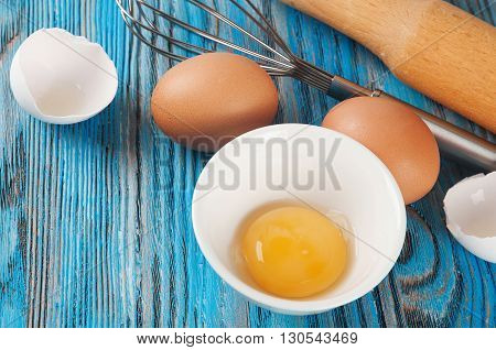 Eggs and egg yolk on a blue wooden background